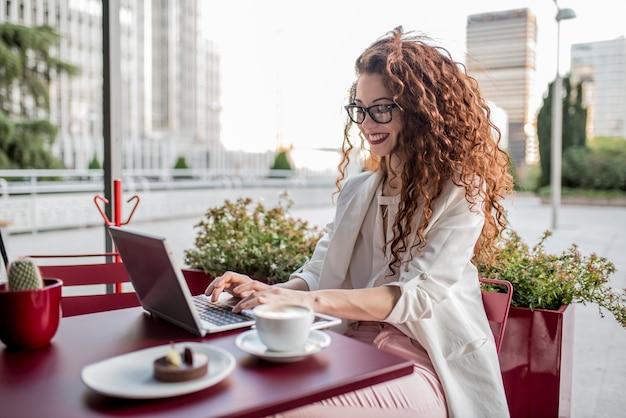 Mujer joven pelirroja de negocios en la computadora