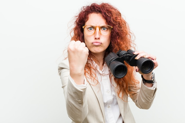 Mujer joven pelirroja de negocios sosteniendo un binoculares mostrando puño