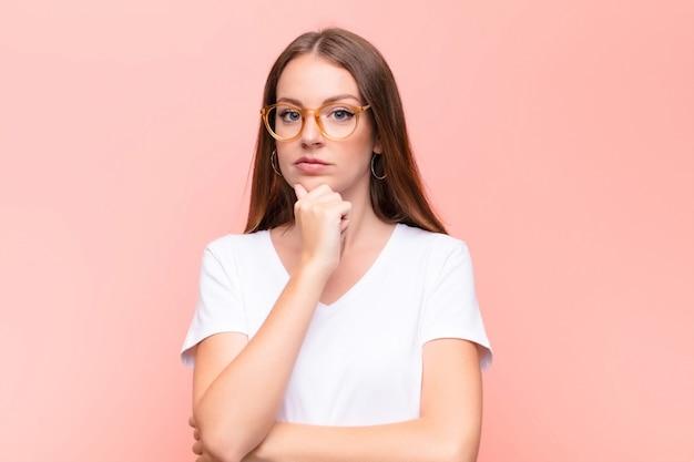 Mujer joven pelirroja que parece seria, confundida, incierta y reflexiva, dudando entre las opciones u opciones sobre la pared