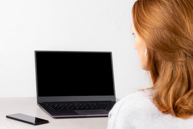Mujer joven pelirroja sentada frente a una computadora portátil con una maqueta negra en la pantalla, concepto de aprendizaje a distancia, transmisión en vivo, comunicación en línea