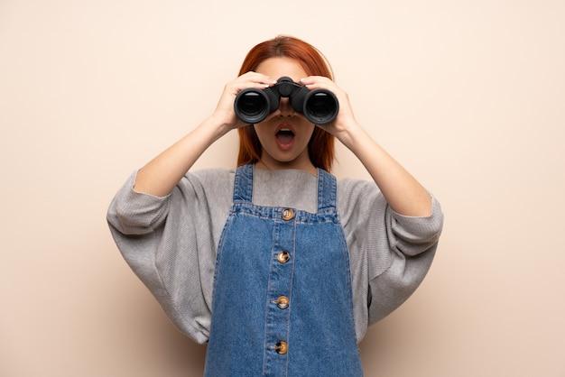 Mujer joven pelirroja sobre aislado y mirando en la distancia con binoculares