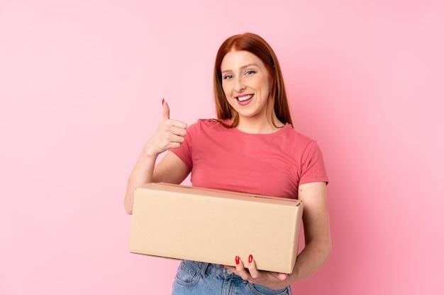 Mujer joven pelirroja sobre pared rosa aislado sosteniendo una caja para moverlo a otro sitio con el pulgar hacia arriba