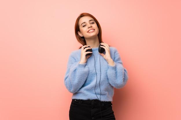 Mujer joven pelirroja sobre rosa con auriculares