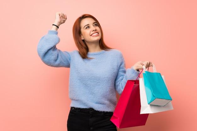 Mujer joven pelirroja sobre rosa con muchas bolsas de compras en posición de victoria