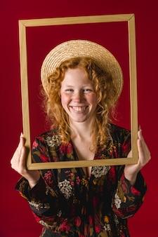 Mujer joven pelirroja sonriendo y sosteniendo el marco de madera
