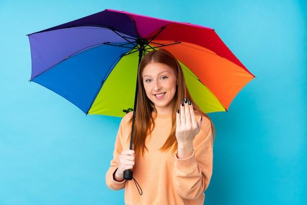 Mujer joven del pelirrojo que sostiene un paraguas sobre la pared aislada que invita a venir con la mano. feliz de que hayas venido