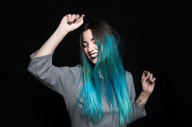 Mujer joven con pelo azul bailando en estudio