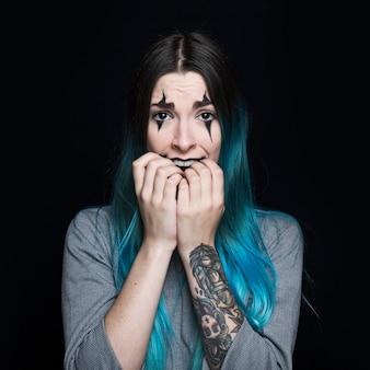 Mujer joven con pelo azul y cara asustada posando en estudio