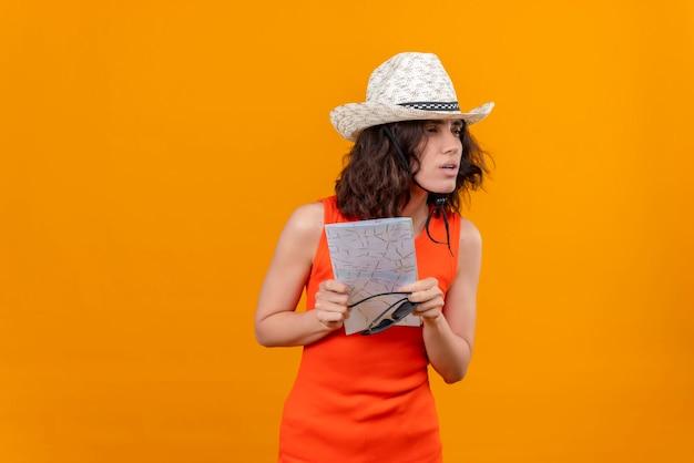 Una mujer joven con el pelo corto en una camisa naranja con sombrero para el sol sosteniendo el mapa con gafas de sol mirando sorprendentemente de lado