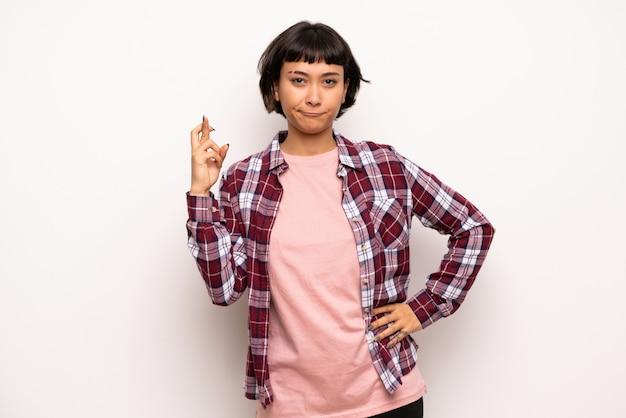 Mujer joven de pelo corto con dedos cruzados y deseando lo mejor.