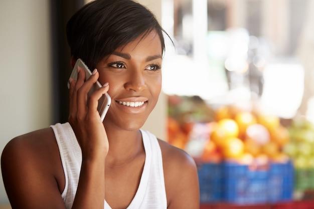 Mujer joven con pelo corto hablando por teléfono