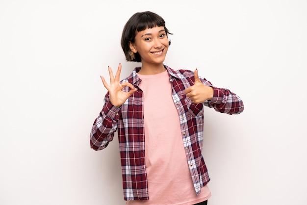 Mujer joven con pelo corto que muestra el signo aceptable con y dando un pulgar hacia arriba gesto