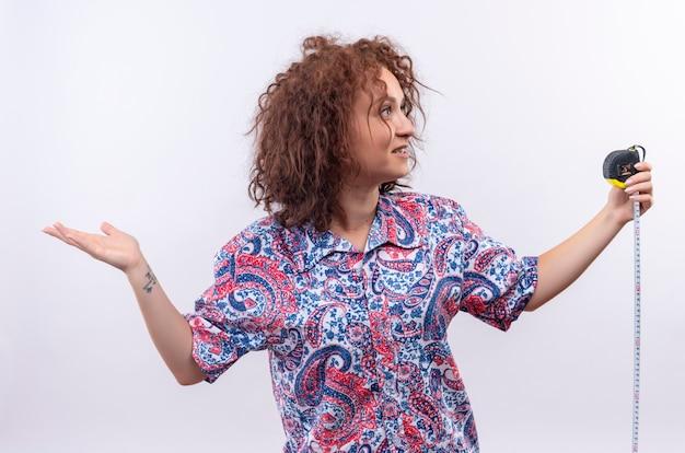Mujer joven con pelo corto y rizado en camisa colorida con cinta métrica mirando confundido, extendiendo los brazos con dudas de pie sobre la pared blanca