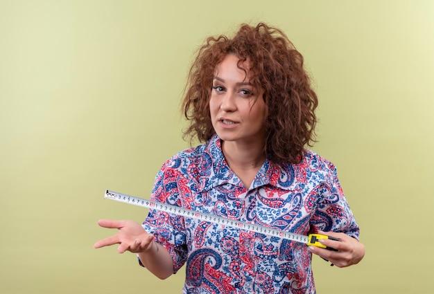 Mujer joven con pelo corto y rizado en camisa colorida con cinta métrica mirando con expresión agresiva de pie sobre la pared verde