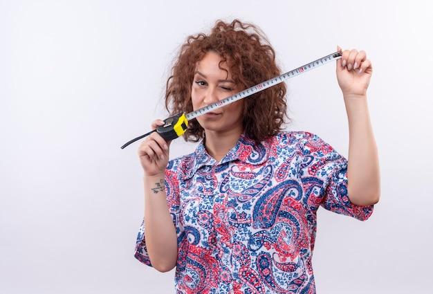 Mujer joven con pelo corto y rizado en camisa colorida con cinta métrica mirando sospechoso parado sobre la pared blanca