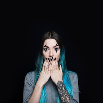 Mujer joven con pelo largo azul cerrando la boca con las manos