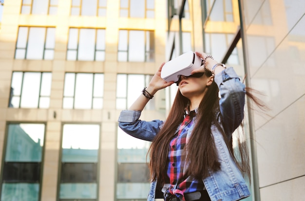 Mujer joven con pelo largo en gafas vr en moderno edificio de cristal