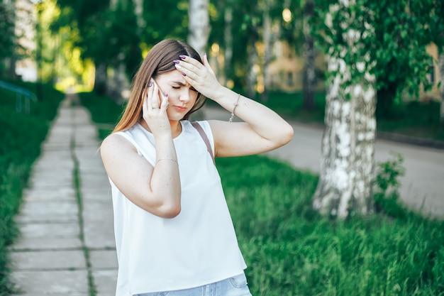 Mujer joven con el pelo largo hablando por teléfono móvil y tiene dolor de cabeza