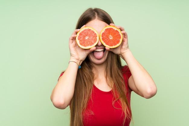 Mujer joven con el pelo largo con rodajas de pomelo como gafas
