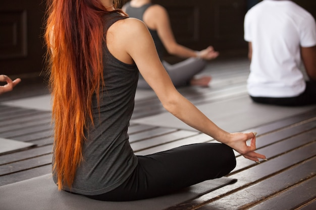 Mujer joven con pelo largo rojo brillante, pose de asiento fácil