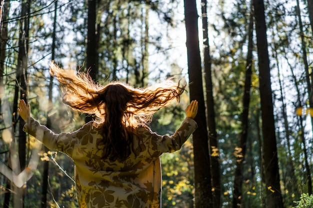 Mujer joven con el pelo largo y rojo en un vestido de lino reuniendo setas en el bosque