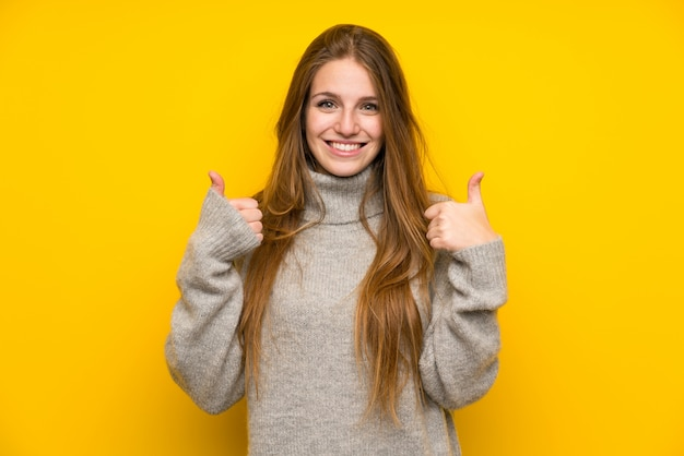 Mujer joven con pelo largo sobre fondo amarillo dando un pulgar arriba gesto