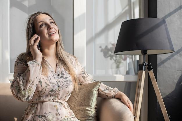 Mujer joven con el pelo largo en un traje de negocios desnudo beige está hablando por teléfono y escribiendo notas
