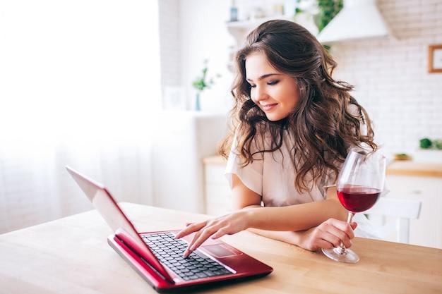 Mujer joven con el pelo oscuro de pie en la cocina y el trabajo. escribiendo en el teclado del portátil. vaso con vino tinto en la mesa. solo en la cocina.