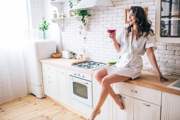 Mujer joven con el pelo oscuro sentado en la cocina y beber vino tinto de vidrio. momento de disfrute solo en la habitación. posando en traje de mañana.