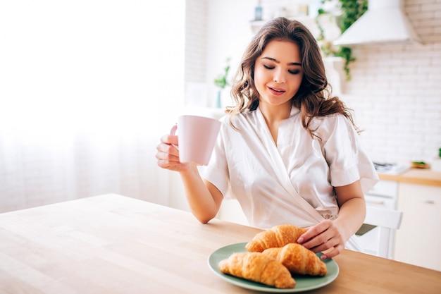 Mujer joven con el pelo oscuro sentado en la cocina y tomando café en la mañana. tomando un croissant y sonríe. modelo encantador.