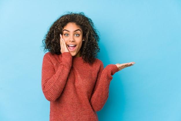 La mujer joven del pelo rizado del afroamericano tiene el espacio en blanco en una palma, mantenga la mano sobre la mejilla.