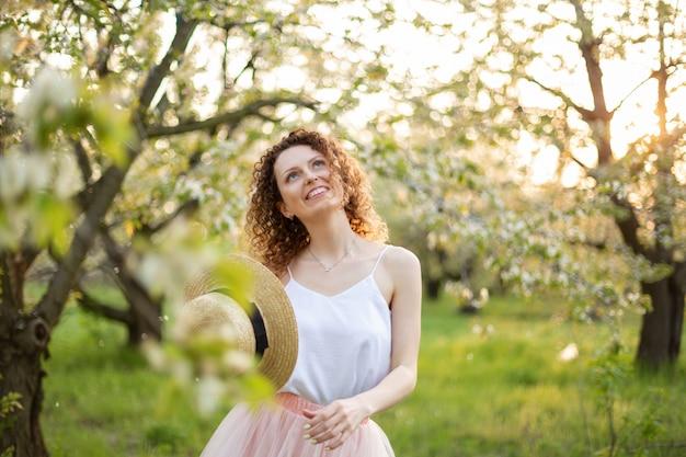 Mujer joven con el pelo rizado caminando en un jardín de flores verdes. humor de primavera