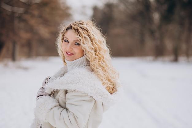 Mujer joven con pelo rizado caminando en un parque de invierno