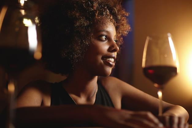 Mujer joven con pelo rizado y una copa de vino tinto
