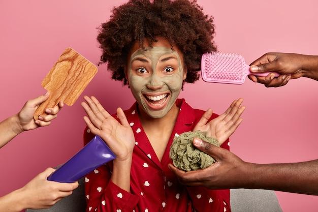 Mujer joven de pelo rizado hace mascarilla limpiadora y exfoliante para la cara