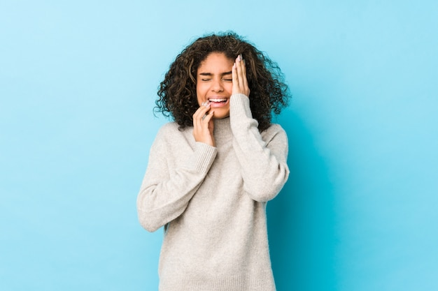Mujer joven de pelo rizado lloriqueando y llorando desconsoladamente.