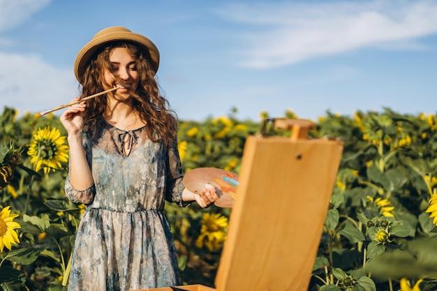 Una mujer joven con el pelo rizado y con un sombrero está pintando en la naturaleza. una mujer se encuentra en un campo de girasol en un hermoso día
