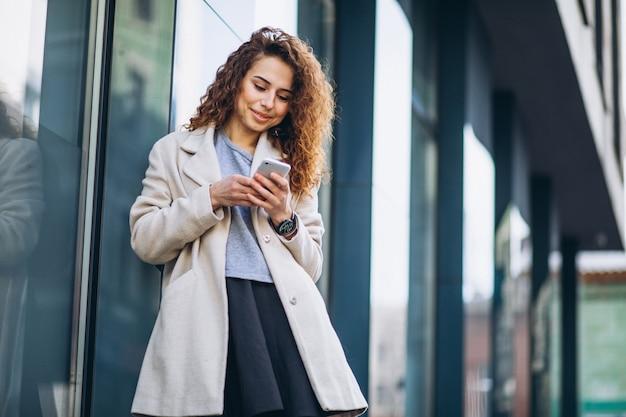 Mujer joven con pelo rizado usando el teléfono en la calle