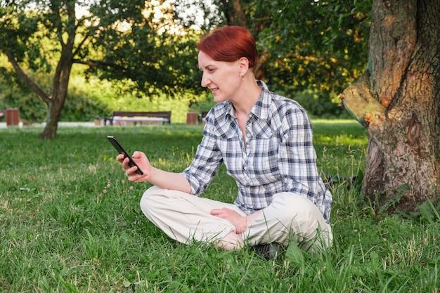 Mujer joven con pelo rojo corto se sienta en el césped en el parque y está enviando mensajes de texto en su teléfono inteligente