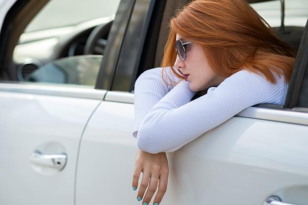 Mujer joven con pelo rojo y gafas de sol viajando en coche. pasajero mirando por la ventana trasera de un taxi en una ciudad.