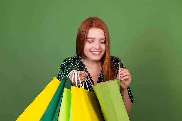 Mujer joven de pelo rojo en la pared verde con bolsas de compras feliz alegre emocionado