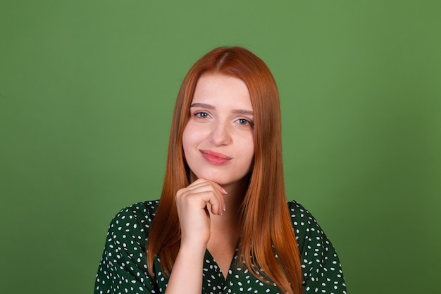 Mujer joven de pelo rojo en la pared verde reflexivo cuestionamiento