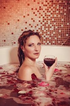 Mujer joven con pelo rojo tomar baño de burbujas con velas.