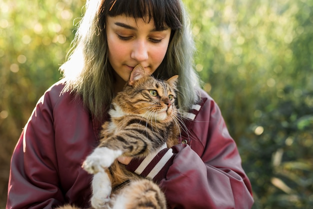 La mujer joven del pelo teñido está abrazando a su gato de gato atigrado en parque