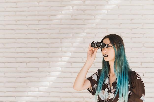 Mujer joven con el pelo teñido mirando a través de binoculares