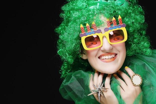 Mujer joven con pelo verde y gafas de carnaval