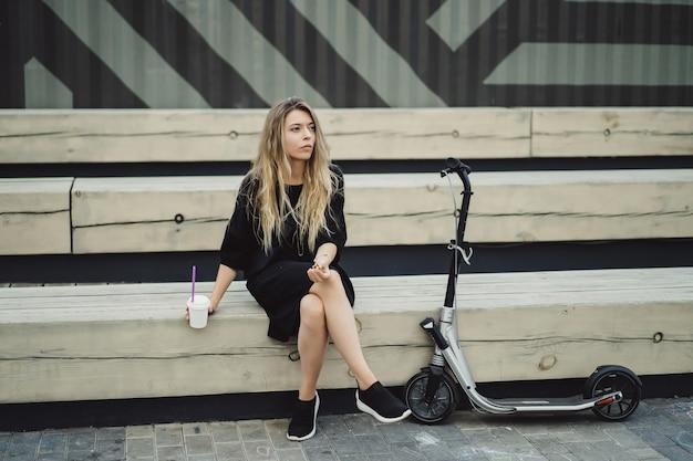 Mujer joven con pelos largos en scooter eléctrico. la niña en el scooter eléctrico bebe café.