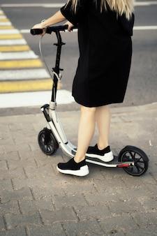Mujer joven con pelos largos en scooter eléctrico. la niña en el scooter eléctrico.