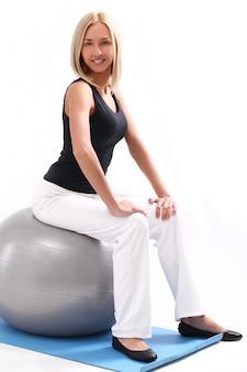 Mujer joven con pelota de fitness
