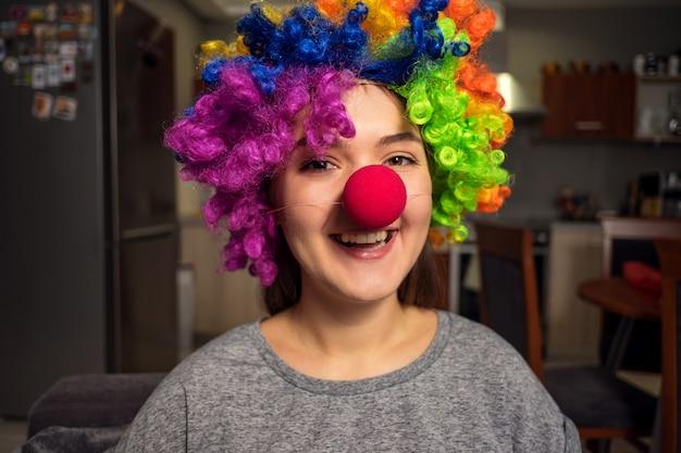 Mujer joven con una peluca de payaso en la cabeza